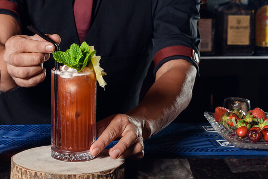 A young professional bartender prepares cocktails for his clients at work. profession concept