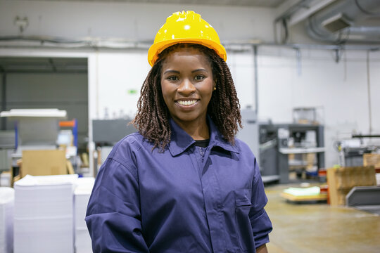 Cheerful African American female factory employee in hardhat and overall standing on plant floor, looking at camera and smiling. Front view, medium shot. Women in industry concept