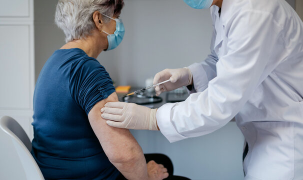 Senior woman being vaccinated against coronavirus by a female doctor