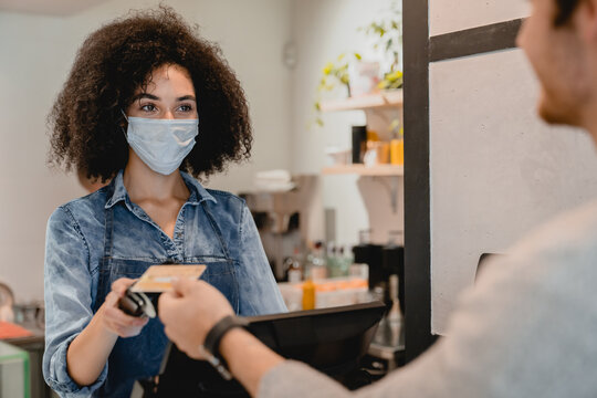 20s attractive afro waitress in medical mask against covid 19 with swiping machine servicing customer in cafeteria