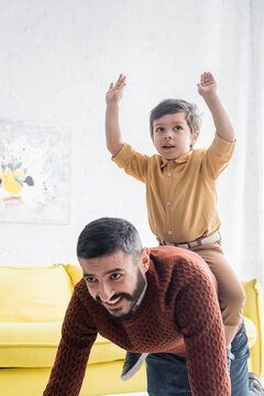 Cheerful boy sitting on back of hispanic grandfather at home, two generations of men