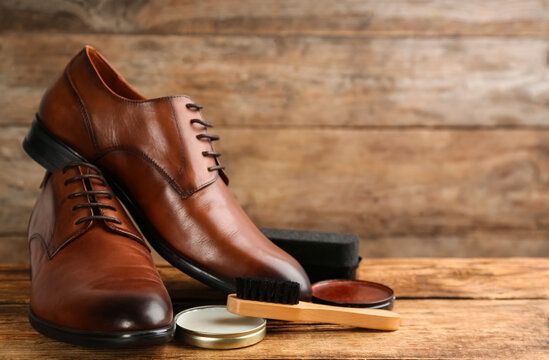 Shoe care products and footwear on wooden table. Space for text