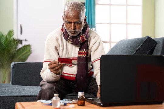 Senior sick old man entering card details for buying medicines online - concept of online medicine shopping.