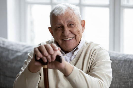 Portrait of happy senior grandfather sitting on couch looking at camera demonstrating white healthy teeth in smile. Satisfied elderly man patient having healthy habit of regular visiting dental clinic