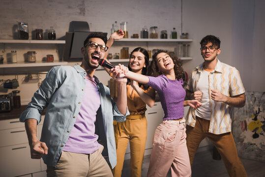 happy hispanic woman dancing with friends and holding microphone near man singing karaoke
