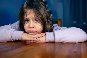 Fototapeta Smutna dziewczynka siedząca przy stole w czasie świąt bożego narodzenia.  obraz