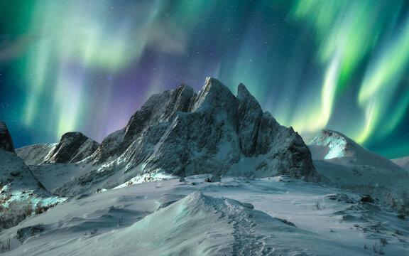 Aurora borealis over majestic mountain in snowy on Segla Island