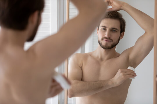 Handsome young 30s shirtless man applying deodorant in arm pit, looking in mirror. Happy millennial man preventing sweating, using underarm antiperspirant after morning showering hygienic routine.
