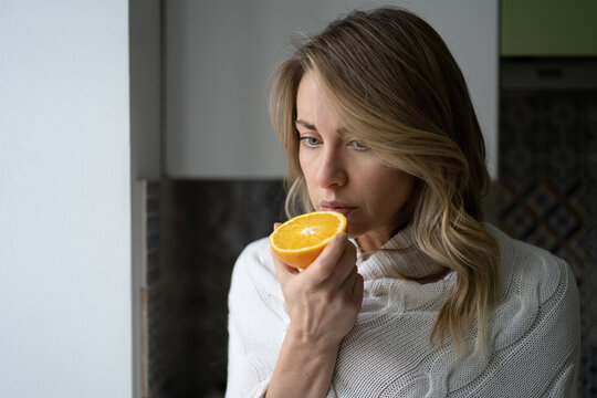 Sick woman trying to sense smell of  half fresh orange, has symptoms of Covid-19, corona virus infection - loss of smell and taste. One of the main signs of the disease.