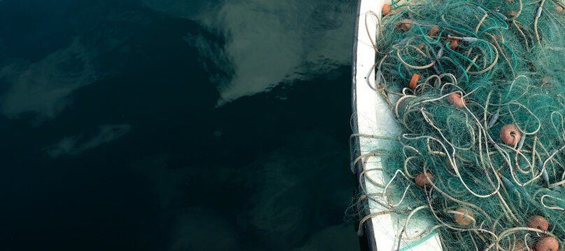 Fishing net in a small fishing boat. Horizontal panoramic crop with large area of dark blue water.