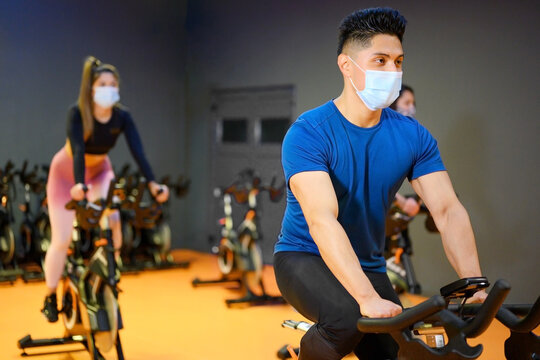 Young People Spinning in the fitness gym with protective face mask during coronavirus outbreak . High quality photo