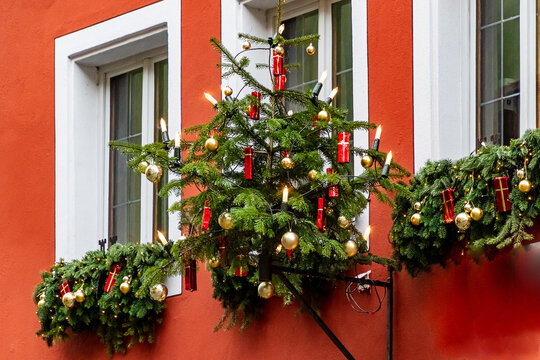 Christmas tree hanging in front of white windows on a red house wall in medieval town of Rothenburg ob der Tauber, Bavaria, Germany