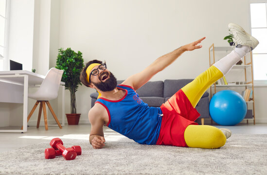 Happy positive funny man working out at home, doing side lying leg lifts and laughing