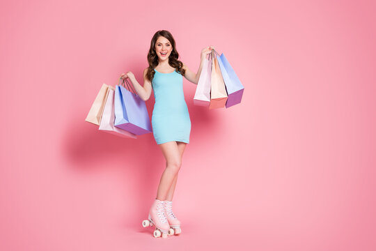 Full size photo of young smiling happy attractive girl woman wear rollers hold bags shopping isolated on pink color background