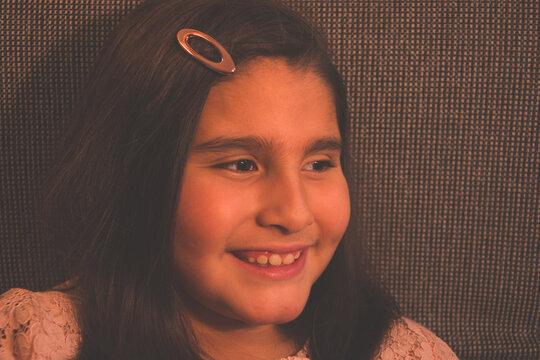 Niña latina sonriente y feliz con clip en el pelo