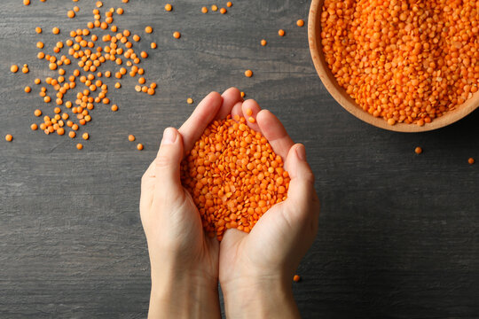 Female hands holds red legumes over a dark background with bowl of legumes