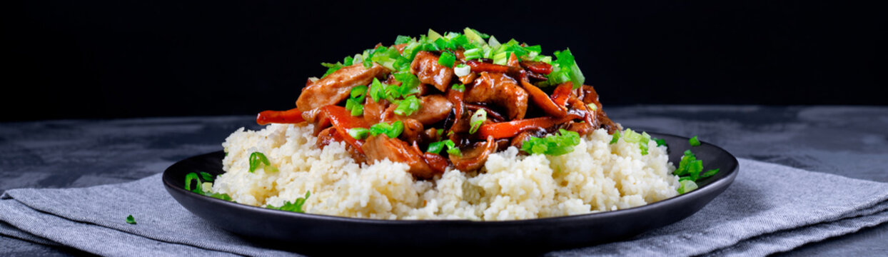 Stir-fried turkey pieces with mushroom, carrot and garlic on couscous. Appetizing hot meal garnished with green onion served on the grey table. Wide banner