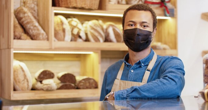 Close up portrait of African American handsome young male seller in mask standing in bakehouse at the counter in bakery shop, looking at camera in good mood. Small business owner. Baker concept