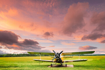 Old Retro Plane Aircraft Aeroplane, Airplane Biplane Parked In Grass Airfield. Altered Sunset Sunrise Sky
