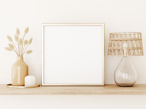 Poster art mockup with square gold metal frame, dried grass in vase, wicker lamp and candle on empty warm beige wall background. Boho interior decoration. 3d rendering, illustration