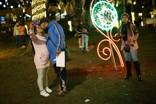 A couple wearing face masks under their chins kiss in a park lit up for the Christmas season, amidst the coronavirus disease (COVID-19) outbreak, in Bogota