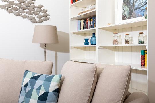 Sofa mit Kissen vor einem Regal mit Büchern