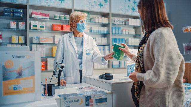 Pharmacy Drugstore Checkout Cashier Counter: Pharmacist and Young Woman Using Contactless Payment Credit Card to Buy Prescription Medicine, Vitamins. People Wearing Protective Face Masks