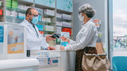 Pharmacy Drugstore Checkout Cashier Counter: Latin Pharmacist and Senior Woman Using Contactless Payment Credit Card to Buy Prescription Medicine, Vitamins. People Wearing Protective Face Masks.
