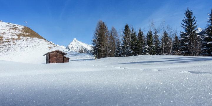 Panorama einer Winterlandschaft mit Skihütte und verschneitem Berg im Hintergrund