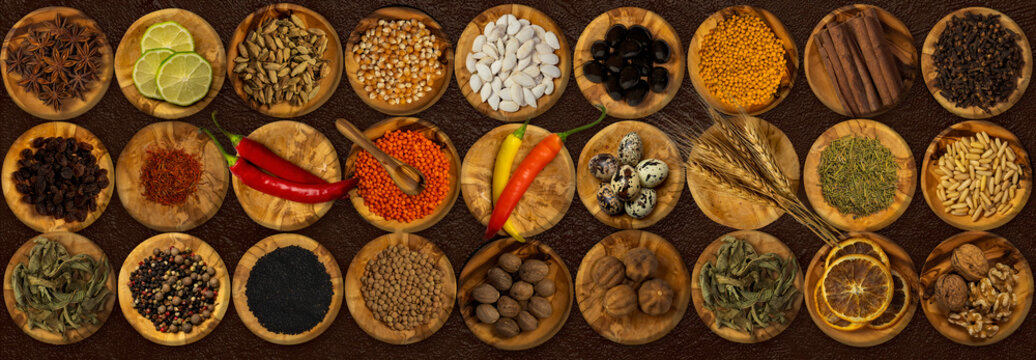 Top view of spices and food ingredients in wooden small plates and a wooden Mortar .