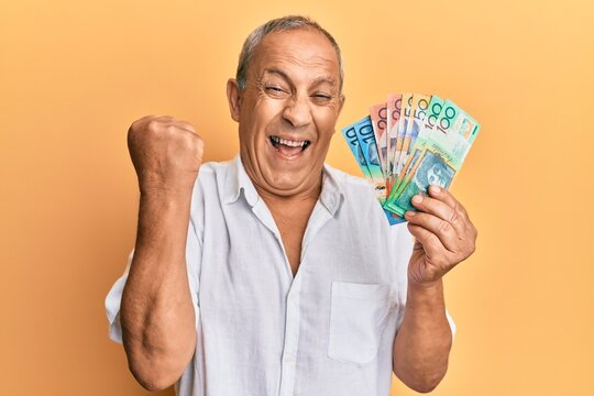 Handsome mature man holding australian dollars screaming proud, celebrating victory and success very excited with raised arm