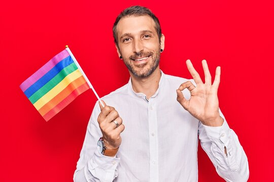 Young handsome man holding rainbow lgbtq flag doing ok sign with fingers, smiling friendly gesturing excellent symbol