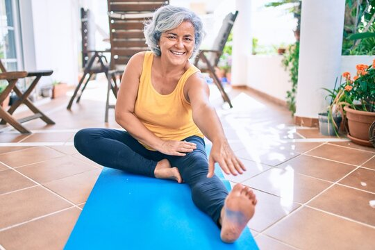 Middle age woman with grey hair smiling happy doing exercise and stretching on the terrace at home