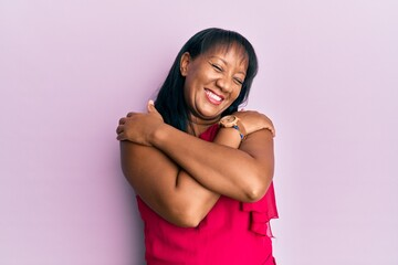 Middle age african american woman wearing casual clothes hugging oneself happy and positive,...