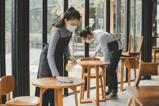 asian waitress staff wearing protection face mask in apron cleaning table with disinfectant spray for protect infection coronavirus (covid-19) in cafe coffee shop restaurant. new normal concept