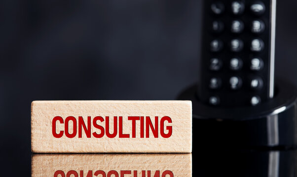 The word consulting service on wooden block with telephone background. Business, financial or legal consulting services concept.