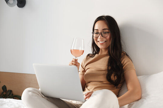 Image of young happy asian woman having video call, sitting on bed and drinking wine while looking at laptop and smiling
