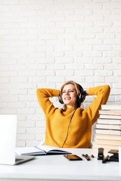 Young woman in yellow sweater and headphones study online using laptop