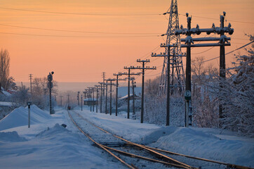 Winter sunset on the railway. Orange sky on a frosty day. Poles with wires along the road. Fotobehang