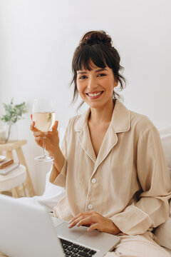 Portrait of smiling woman using laptop at home and enjoying wine