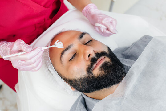 A young man is undergoing a cosmetic facial peeling procedure. Cosmetology and rejuvenation