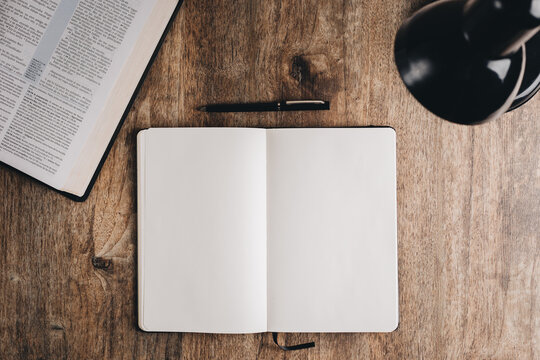 Blank notebook for bible study on a wooden desk. Top view flat lay.