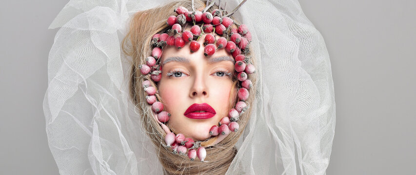 beautiful woman face with professional makeup, frosty winter beauty. close up portrait. surrounded by red berries