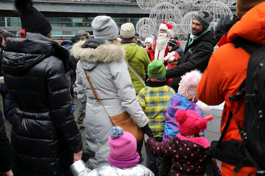 A mask-less Santa Claus poses with children from an unmasked group protesting against coronavirus disease (COVID-19) restrictions in Toronto