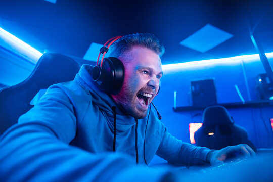 Streamer young man angry screams defeat professional gamer playing online games computer with headphones, neon color