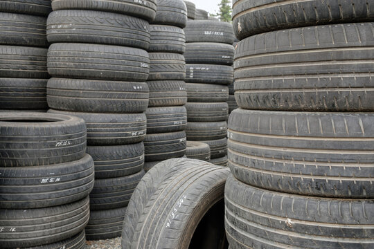 Stack of old used car tires on the ground, selective focus