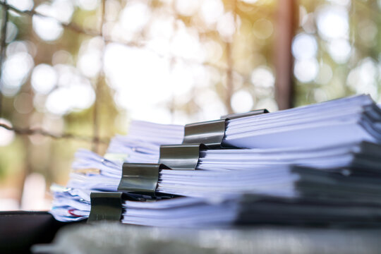 Piles of stack unfinished documents reports files with overwork paperwork on teacher desk. Messy sheet book assessment legal folder at business tax audit, work from home when covid-19 pandemic