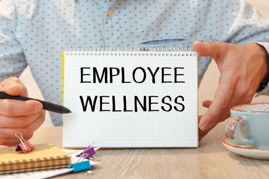 Employee Wellness is written on a notepad on office desk