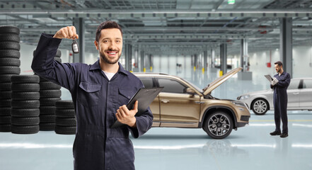 Mechanic holding a key in an auto repir garage and other worker checking cars Wall mural