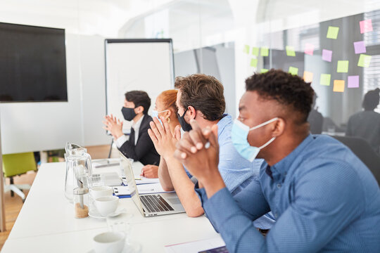 Business people in conference room with mask